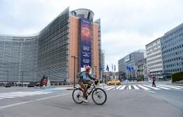 Een fietser aan het Berlaymontgebouw in de Europese wijk. Er is bijna geen verkeer door de lockdownmaatregelen van de overheid om covid-19, de ziekte veroorzaakt door het coronavirus, in te dijken